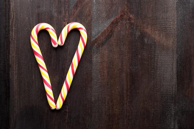 Lollys in hartvorm op houten achtergrondexemplaarruimte Premium Foto