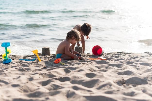 Long shot broers en zussen maken zandkastelen op het strand Gratis Foto