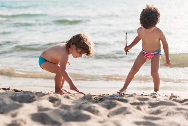Long shot van kinderen spelen op het strand Gratis Foto