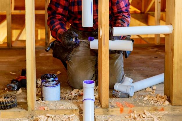 Loodgieter handen in lijm twee stukken plastic afvoerpijp pvc-buis, close-up op nieuwe badkamer Premium Foto