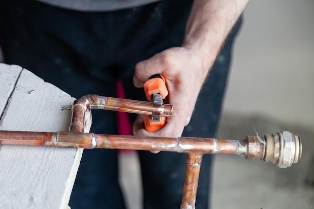 Loodgieter van de de loodgietersarbeider van de close-up snijdt de professionele pijp en houdt het met buigtang. Premium Foto