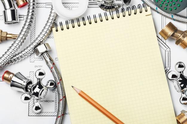 Loodgieterswerk en hulpmiddelen met een notitieboekje Premium Foto