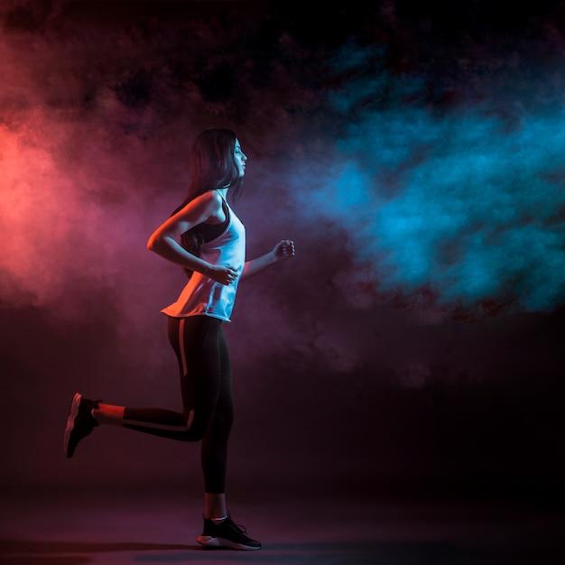 Lopende vrouw in donkere studio Gratis Foto