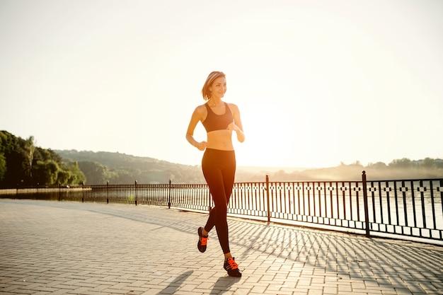 Lopende vrouw. runner joggen in zonnig helder licht. vrouwelijke fitness model training buiten in het park Gratis Foto