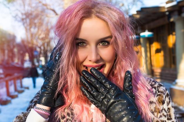Ð¡lose-up portret van mooie vrouw met roze ongebruikelijke golvende haren, poseren op de besneeuwde straat in de winter, mooie ogen, glimlach en stijlvolle leren handschoenen met studs, rock stijl. Gratis Foto