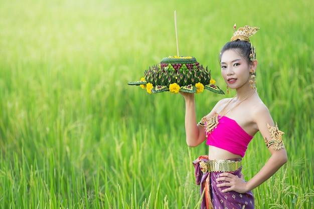 Loy krathong festival; vrouw in thaise traditionele outfit met versierde drijfvermogen Gratis Foto
