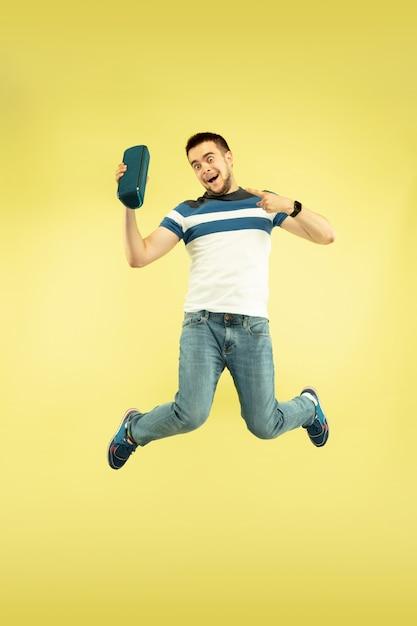Lucht geluid. volledig lengteportret van gelukkige springende mens met gadgets op gele achtergrond. moderne technologie, concept van vrijheid van keuzes, concept van emoties. gebruik een draagbare luidspreker als een superheld tijdens de vlucht. Gratis Foto