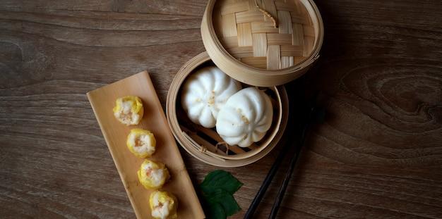 Lucht schot van chinese gestoomde bol en gestoomd varkensvleesbroodje in een bamboestoomboot met eetstokje Premium Foto