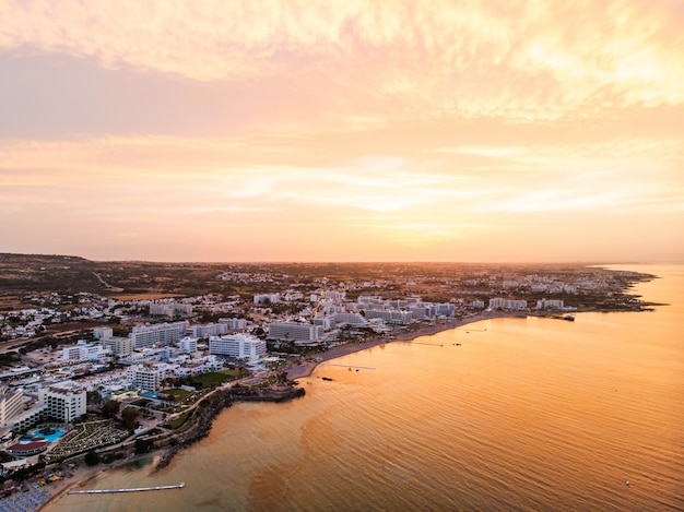 Luchtdiehommel van de zonsondergang boven protaras-stad wordt geschoten Premium Foto