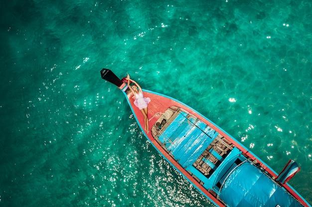 Luchtdiehommel van een jonge blondevrouw in een roze kleding en zonnebril in de voorzijde van een houten longtail thaise boot wordt geschoten. kristalhelder water en koralen op een tropisch eiland en een geweldig strand. Premium Foto