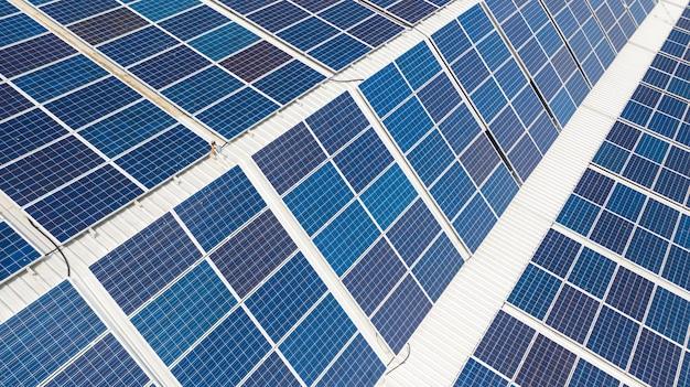 Luchtfoto bovenaanzicht van de zonnecellen op het dak, zonnepanelen geïnstalleerd op een dak van een groot industrieel gebouw of een magazijn Premium Foto