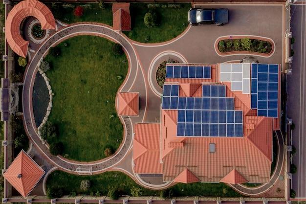 Luchtfoto bovenaanzicht van nieuwe moderne woonhuis cottage met blauwe panelen. hernieuwbare ecologische groene energieproductie concept. Premium Foto