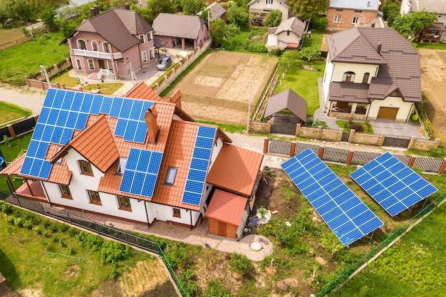Luchtfoto bovenaanzicht van nieuwe moderne woonhuis huisje met blauwe glanzende zonne-fotovoltaïsche panelen systeem op dak. hernieuwbaar ecologisch concept voor de productie van groene energie. Premium Foto