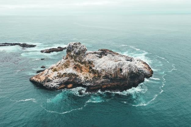 Luchtfoto drone shot van een klein rotsachtig eiland in de blauwe prachtige oceaan Gratis Foto