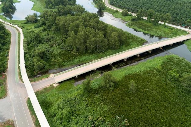 Luchtfoto drone shot van weg tussen groen veld zomer bos en rivier en meer ik Premium Foto