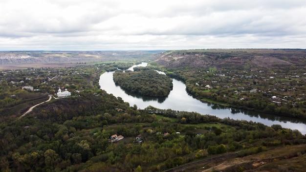 Luchtfoto drone uitzicht op de natuur in moldavië, drijvende rivier met als gevolg van bewolkte hemel en dorp in de buurt, heuvels met bomen Gratis Foto