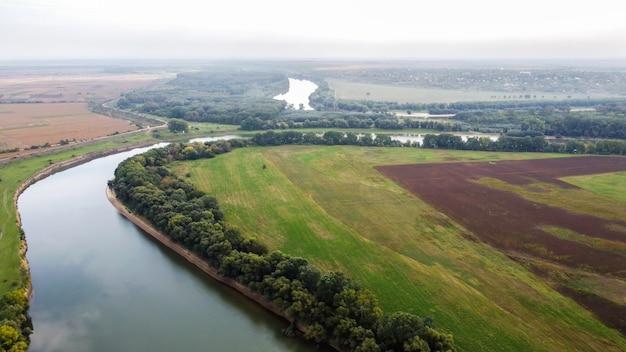 Luchtfoto drone uitzicht op de natuur in moldavië, drijvende rivier met reflecterende lucht, groene velden met bomen, mist in de lucht Gratis Foto