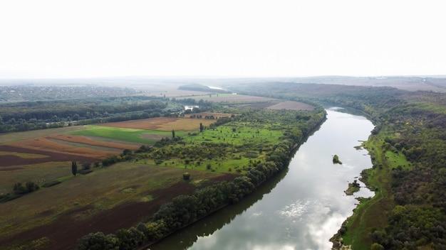 Luchtfoto drone uitzicht op de natuur in moldavië, drijvende rivier met reflecterende lucht, groene velden met bomen, mist in de lucht Premium Foto