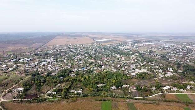 Luchtfoto drone uitzicht op dorp in moldavië, meerdere gebouwen en bomen, mist in de lucht Gratis Foto