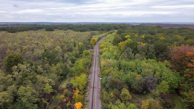 Luchtfoto drone-weergave van de natuur in moldavië, een spoorlijn die door een dicht bos, bewolkte hemel gaat Gratis Foto