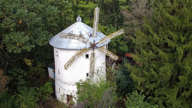 Luchtfoto drone-weergave van een oude windmolen omgeven door groene bomen in een bos in moldavië Gratis Foto