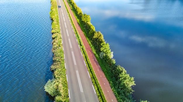 Luchtfoto drone weergave van snelweg weg en fietspad op polder dam, autoverkeer van bovenaf, noord-holland, nederland Premium Foto
