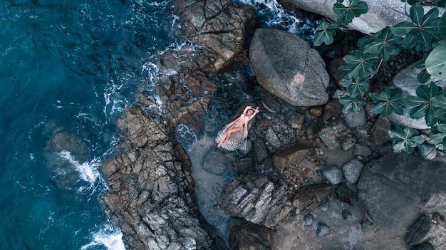 Luchtfoto: foto van een mooi poseren meisje liggend in een witte jurk, tussen de rotsen in de buurt van de zee. Premium Foto