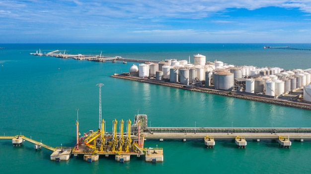 Luchtfoto laadarm olie- en gasraffinaderij in commerciële haven, tankterminal met veel olieopslagtank en petrochemische opslagtank in de haven, industriële tankopslag luchtfoto. Premium Foto