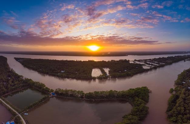 Luchtfoto mekong river delta regio, ben tre, zuid-vietnam. waterkanalen en tropische rivieren dramatische hemel bij zonsondergang. Premium Foto
