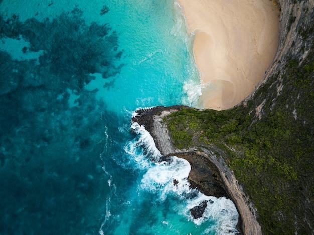 Luchtfoto van de kliffen bedekt met groen omgeven door de zee - perfect voor achtergronden Gratis Foto