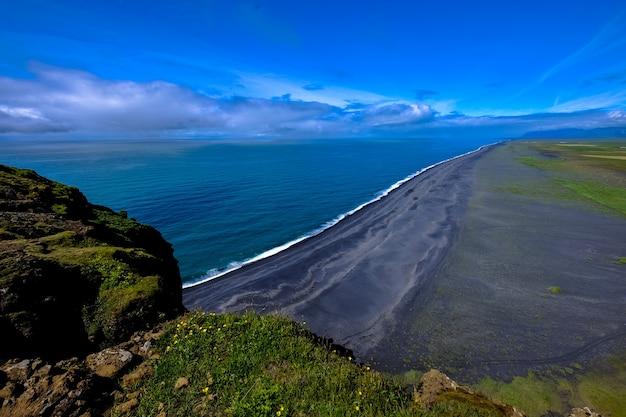 Luchtfoto van de kustlijn in de buurt van de berg onder een blauwe hemel overdag Gratis Foto