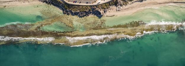 Luchtfoto van de prachtige oceaangolven die het strand ontmoeten Gratis Foto