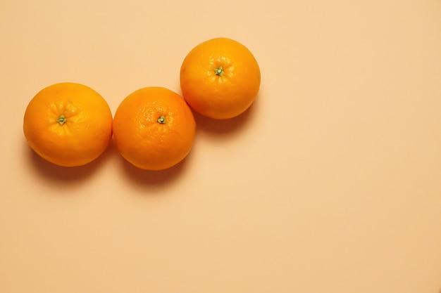 Luchtfoto van drie heerlijk oranje fruit met oranje kleur op de achtergrond Gratis Foto