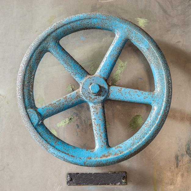 Luchtfoto van een blauw antiek wiel op een betonnen vloer overdag Gratis Foto