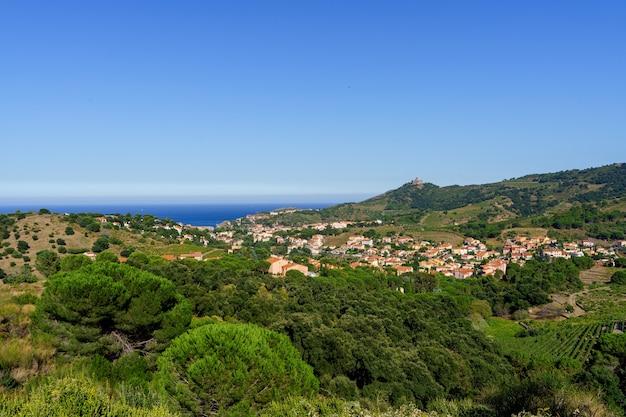 Luchtfoto van een dorp midden in een vallei met uitzicht op zee. colliure, frankrijk Premium Foto