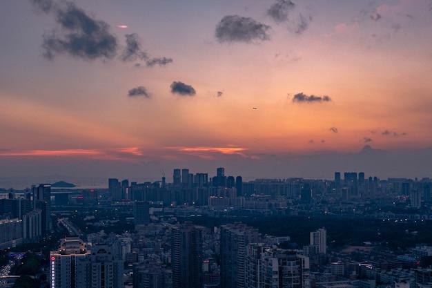 Luchtfoto van een grote stad onder een oranjeblauwe bewolkte hemel bij zonsondergang Gratis Foto
