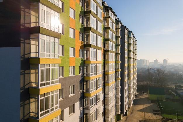 Luchtfoto van een hoog woonappartementengebouw met veel ramen en balkons. Premium Foto