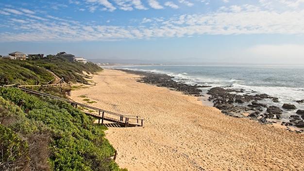 Luchtfoto van een houten pad dat naar het strand komt door de adembenemende oceaan Gratis Foto