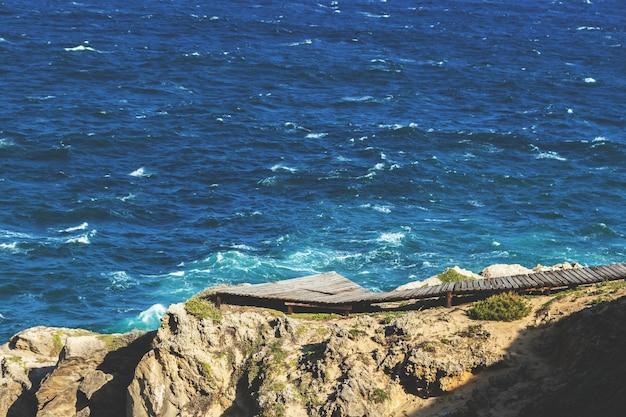 Luchtfoto van een houten pad op de rotsen boven de oceaan Gratis Foto