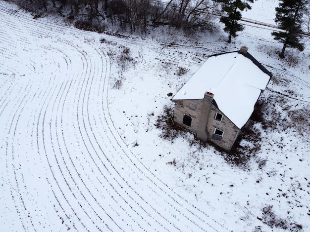 Luchtfoto van een landelijk huis met velden bedekt met sneeuw Gratis Foto