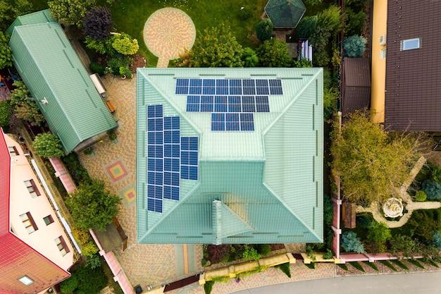 Luchtfoto van een landelijk privéhuis met fotovoltaïsche zonnepanelen voor het produceren van schone elektriciteit op dak autonoom huis in woonwijkconcept Premium Foto
