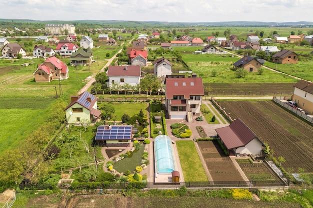 Luchtfoto van een privéwoning in de zomer met blauwe fotovoltaïsche zonnepanelen op het dak en in de tuin. Premium Foto