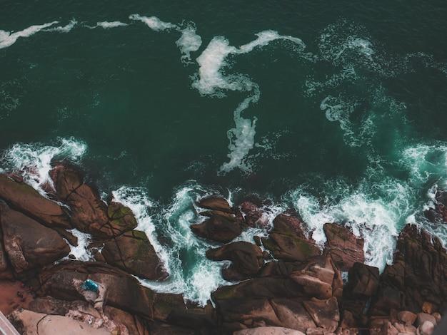 Luchtfoto van een rotsstrand en de zee met waterspatten Gratis Foto