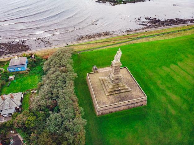 Luchtfoto van een standbeeld in de groene vallei nabij de zee Gratis Foto