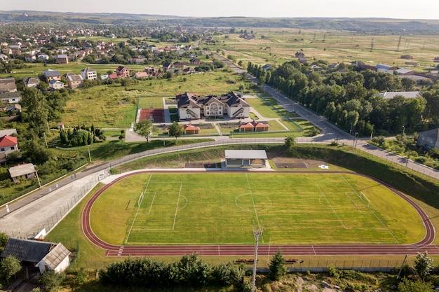Luchtfoto van een voetbalveld op een stadion bedekt met groen gras in landelijke stad. Premium Foto