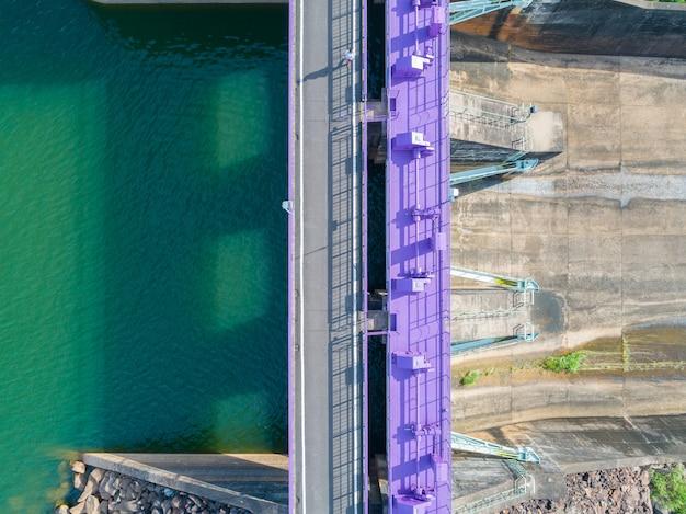 Luchtfoto van een waterkrachtcentrale en dam, topview hydraulische slagboomdeur - betonnen waterkering stroomafwaarts helling. Premium Foto