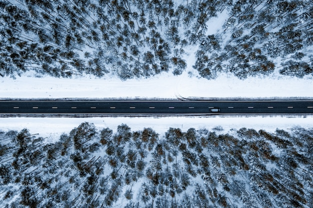 Luchtfoto van een weg in een bos bedekt met de sneeuw tijdens de winter Gratis Foto