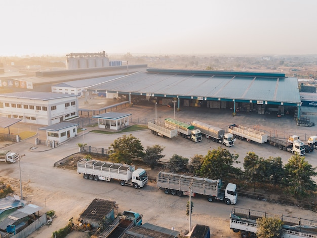 Luchtfoto van fabrieksvrachtwagens geparkeerd in de buurt van het magazijn overdag Gratis Foto