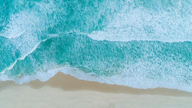 Luchtfoto van golven breken op de kust. kleurrijke strand zomer. Premium Foto