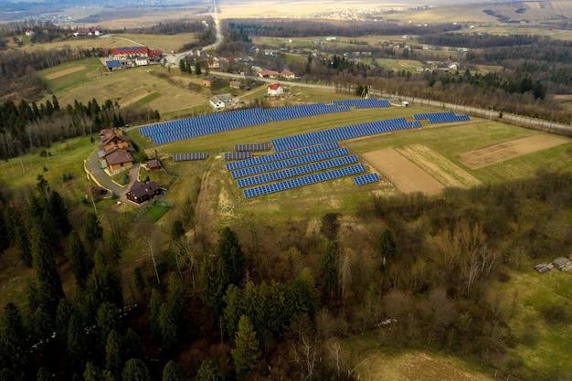 Luchtfoto van groot gebied van zonne-fotovoltaïsche panelen systeem produceren van hernieuwbare schone energie op groen gras Premium Foto